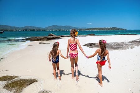 traje de baño: Tres niños jugando en la playa tropical, visión trasera Foto de archivo