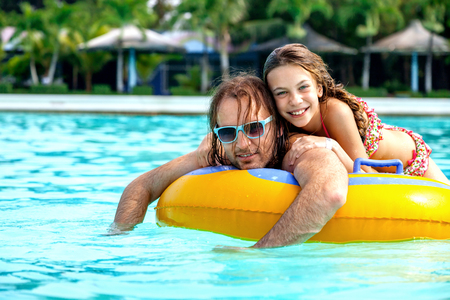 tween: Father having fun with her tween daughter on the inflatable ring in the water park together