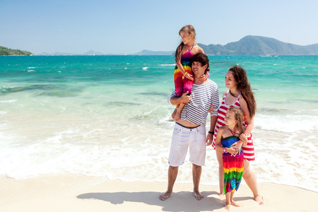 mom dad: Madre, padre y dos de sus hijos caminando en la playa tropical