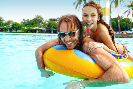 hotel with pool: Father having fun with her tween daughter on the inflatable ring in the water park together