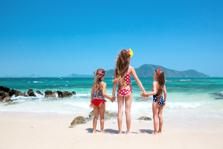 Three kids playing at the tropical beach, rear view Stock Photo