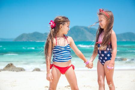 traje de bano: Dos niños jugando en la playa tropical