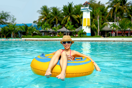 pool preteen: Tween girl relaxing on the inflatable ring in the water park in Thailand