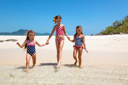 traje de baño: Tres niños que juegan en la playa tropical