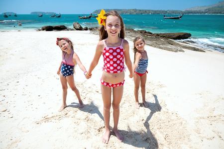 Tres niños que juegan en la playa tropical Foto de archivo - 52622827