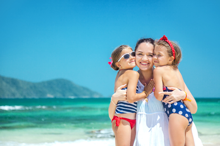 Mom with her two children having fun at the tropical beach