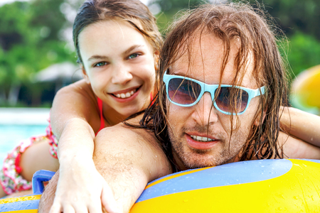 father daughter: Father having fun with her tween daughter on the inflatable ring in the water park together