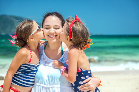 kisses: Mom with her two children having fun at the tropical beach, daughters kissing mother