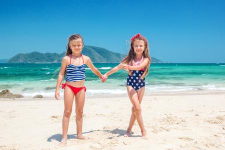 petite fille maillot de bain: Deux enfants jouant sur la plage tropicale