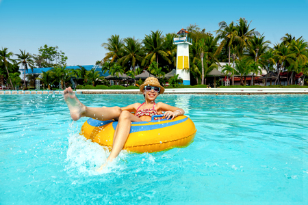 aquapark: Tween girl relaxing on the inflatable ring in the water park in Thailand