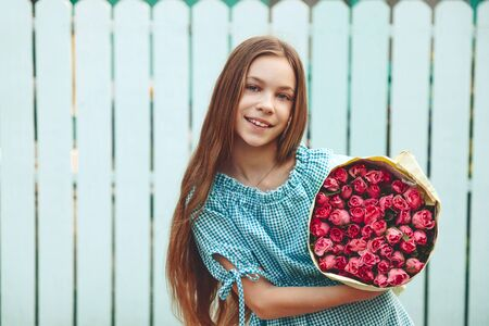 tween: Tween girl holding a bunch of pink roses wrapped in craft paper over blue wooden fence