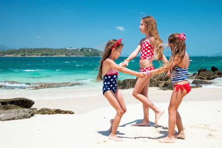 Three kids playing at the tropical beach Stock Photo