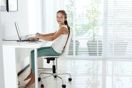 pre adolescent girls: Tween girl using laptop at the table in the room