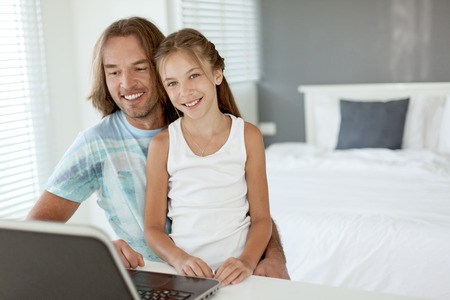 pedagogy: Pre teen daughter came to her dad when he was using laptop in home room. Father browsing internet with child together. Stock Photo