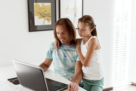 Pré fille adolescente est venu à son père quand il utilisait un ordinateur portable dans la chambre de la maison. Père navigation internet avec enfant ensemble.