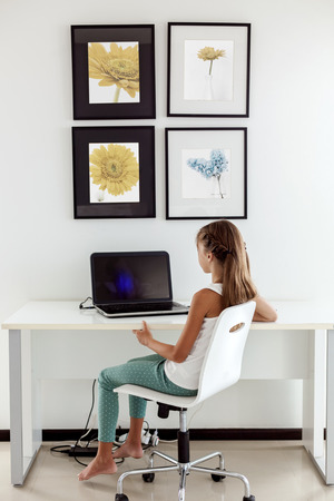 tween: Tween girl using laptop at the table in the room