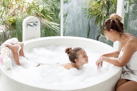 bañarse: Madre lavando a su hijo en el hotel de lujo de baño al aire libre con una espuma, la naturaleza muerta