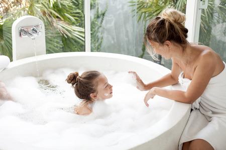 child bath: Mom washing her child in luxury hotel outdoor bath with a foam, still life