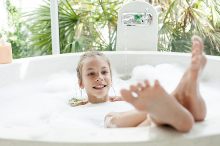 Kid girl washing with a foam in luxury hotel outdoor bath, still life Stock Photo