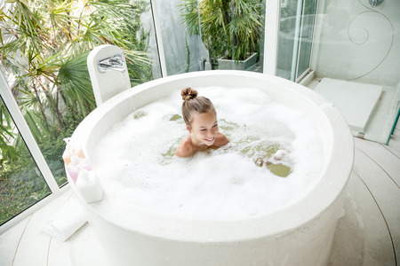 everyday people: Kid girl washing with a foam in luxury hotel outdoor bath, still life Stock Photo