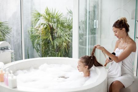 Moeder haar borstelen van haar kind in een luxe hotel in openlucht bad met een schuim, stilleven Stockfoto
