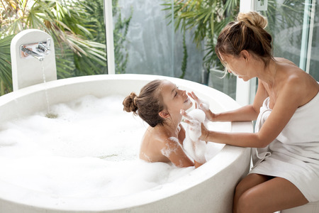泡、静物で高級ホテルの露天風呂で彼女の子供を洗うママ