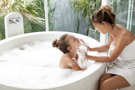 Mom wassen van haar kind in een luxe hotel in openlucht bad met een schuim, stilleven Stockfoto