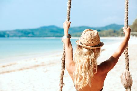 columpio: Ni�a sentada en el columpio en la playa tropical, isla del para�so