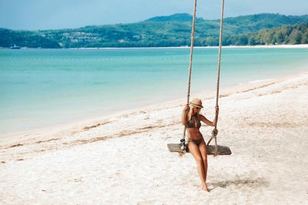 island paradise: Girl sitting on the swing on the tropical beach, paradise island