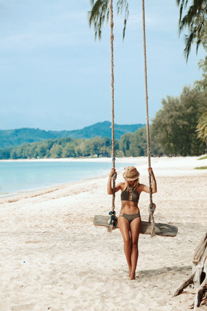 asian bikini: Girl sitting on the swing on the tropical beach, paradise island