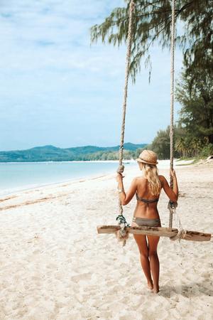 소녀 열대 해변에서 스윙에 앉아 낙원의 섬 스톡 콘텐츠