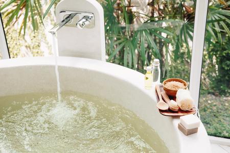 water closet: Spa decoration, natural organic products on a bathtube. Loofah, towel and frangipani flower. Stock Photo