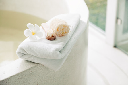 Spa decoration, natural organic products on a bathtube. Loofah, towel and frangipani flower. Stock Photo