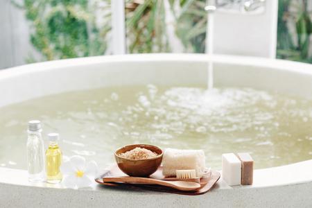 sal: Decoración del balneario, productos orgánicos naturales en una bañera. Esponja vegetal, toalla y flor de frangipani