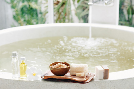 Spa decoration, natural organic products on a bathtube. Loofah, towel and frangipani flower