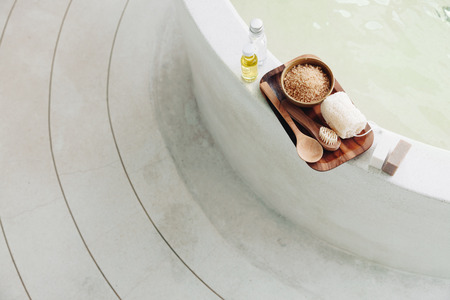aromas: Spa decoration, natural organic products on a bathtube. Loofah, towel and frangipani flower, top view