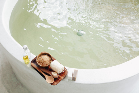 decorazione Spa, prodotti biologici naturali su una vasca da bagno. Luffa, asciugamano e fiore del frangipani, vista dall'alto