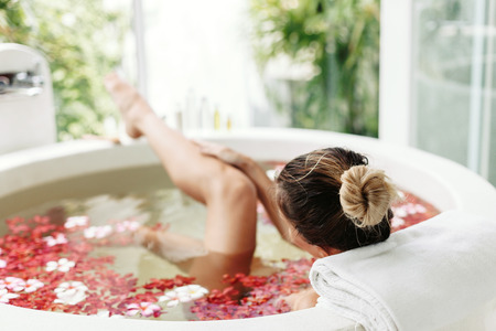 Woman relaxing in round outdoor bath with tropical flowers, organic skin care, luxury spa hotel, lifestyle photo Stock Photo