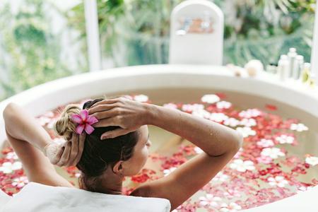 Femme de détente dans le bain en plein air rond avec des fleurs tropicales, les soins de la peau organique, hôtel spa de luxe, style de vie photo Banque d'images