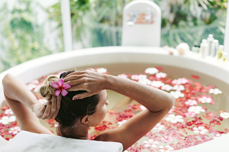 take a bath: Woman relaxing in round outdoor bath with tropical flowers, organic skin care, luxury spa hotel, lifestyle photo Stock Photo