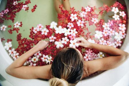 Mulher que relaxa no banho ao ar livre redonda com flores tropicais, cuidados com a pele orgânica, hotel spa de luxo, estilo de vida foto, vista de cima