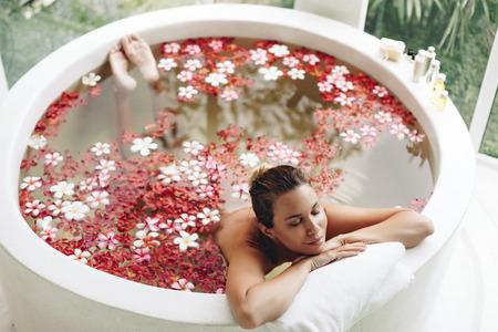 bañarse: Mujer que se relaja en el baño al aire libre redondo con flores tropicales, cuidado de la piel orgánica, hotel spa de lujo, el estilo de vida foto, vista desde arriba