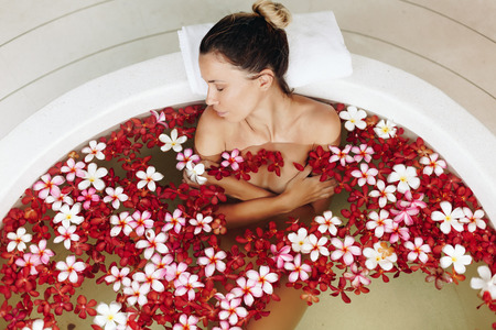 take a bath: Woman relaxing in round outdoor bath with tropical flowers, organic skin care, luxury spa hotel, lifestyle photo, top view