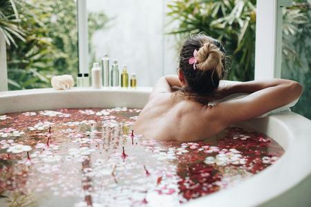Donna che si distende nel bagno all'aperto rotonda con fiori tropicali, la cura della pelle organici, hotel spa di lusso, stile di vita foto