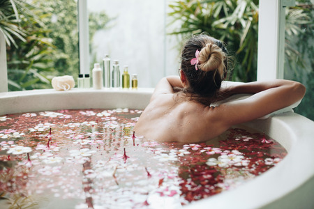 Femme de détente dans le bain en plein air rond avec des fleurs tropicales, les soins de la peau organique, hôtel spa de luxe, style de vie photo