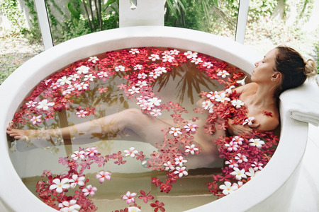 Woman relaxing in round outdoor bath with tropical flowers, organic skin care, luxury spa hotel, lifestyle photo, top view