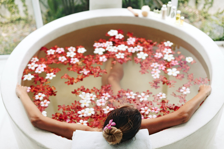 taking bath: Woman relaxing in round outdoor bath with tropical flowers, organic skin care, luxury spa hotel, lifestyle photo, top view