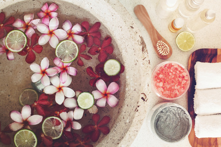 foot spa: Foot bath in bowl with lime and tropical flowers, spa pedicure treatment, top view Stock Photo
