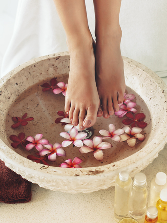 Foot bath in bowl with tropical flowers and oil, spa pedicure treatment Standard-Bild