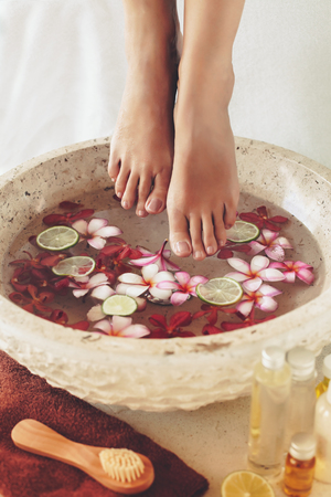Foot bath in bowl with lime and tropical flowers, spa pedicure treatment